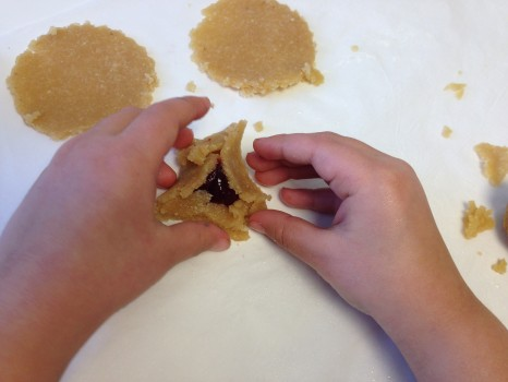 Shaping the dough into triangles around the raspberry jam.