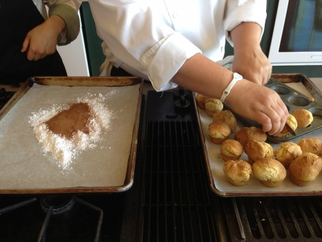 They tossed the hot doughnut holes in a cinnamon/icing sugar mix.