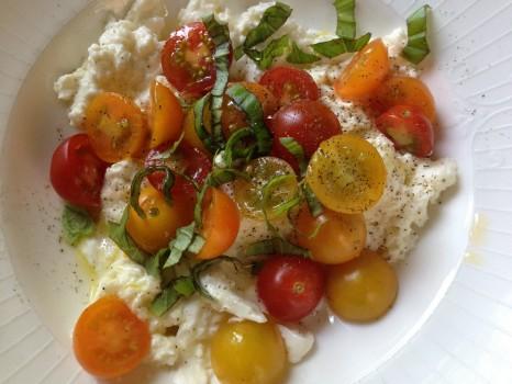 Tomato burrata salad: cherry tomatoes, burrata cheese, fresh basil ribbons, olive oil, pepper, sea salt
