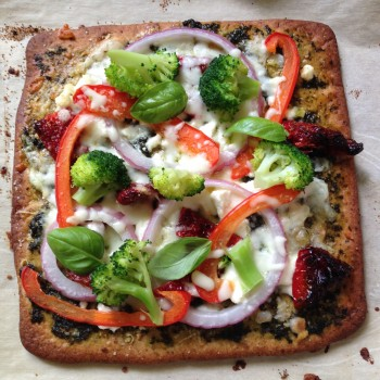 Homemade pizza with O'Doughs Flax Pizza Crust topped with goat cheese, Parmesan, red peppers, red onion, broccoli and sundried tomatoes.